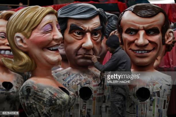 A man puts the final touche on a giant figure depicting rightwing presidential candidates Francois Fillon next to others depicting far right...