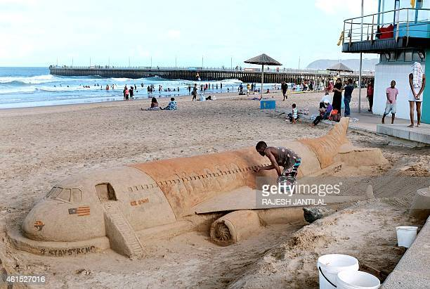 A man puts the final touches on a sand sculpture in memory of the victims of AirAsia flight QZ8501 at North Beach in Durban on January 14 2015...