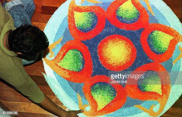 A man puts the finishing touch to a traditional Indian Kolam made of dried rice at a hotel in Kuala Lumpur 16 October 2000 The Kolam is an Indian...
