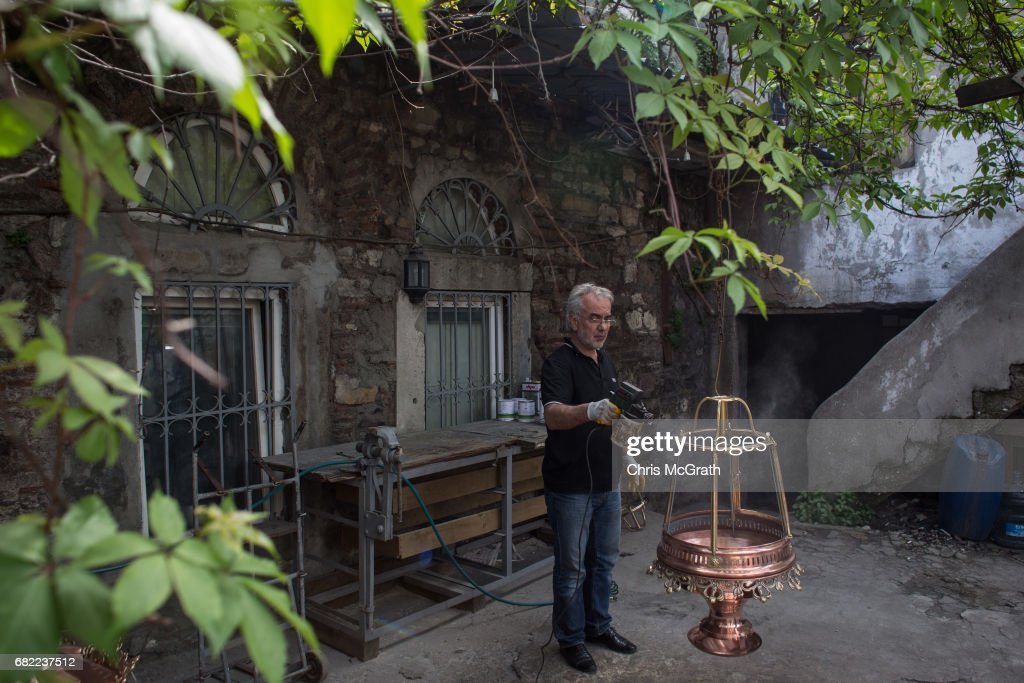 A Man Puts The Finishing Touches On A Decorative Light At