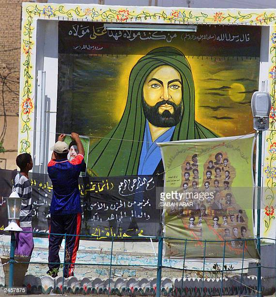 A man puts up a poster of slain Ayatollah Mohammed Baqr alHakim in front of a new billboard of Imam Ali the first Shiite Imam 01 September 2003 in...