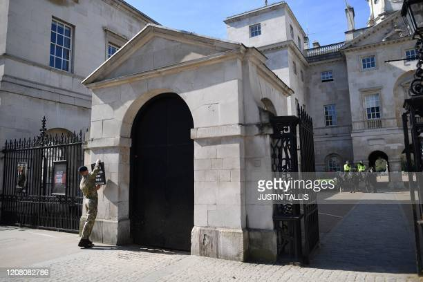 A man puts up a sign at the entrance to the Horse Guards on a deserted Whitehall in central London on the morning on March 24 2020 after Britain...