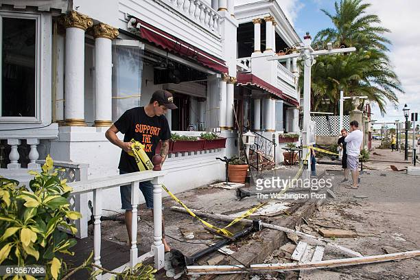 A man puts up caution tape as people walk by and take photos of the Casablanco Inn the day after Hurricane Matthew hit St Augustine FL on Saturday...