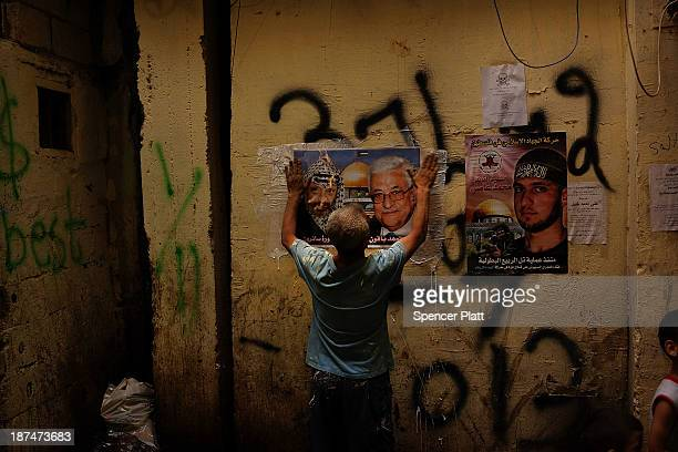 A man puts up pictures of the late Palestinian leader Yasser Arafat and Palestinian President Mahmoud Abbas in a neighborhood with a high...