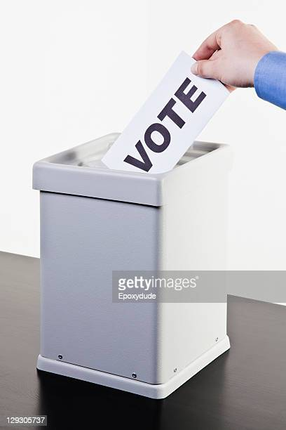 A man putting a ballot with the word VOTE written on it into a ballot box, close-up hands