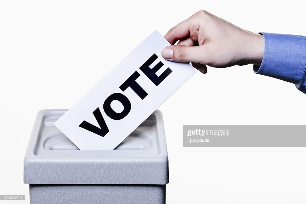 A man putting a ballot with the word VOTE written on it into a ballot box, close-up hands : Stock Photo
