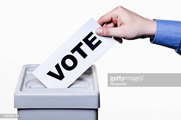 a man putting a ballot with the word vote written on it into a ballot box, close-up hands - election stock pictures, royalty-free photos & images