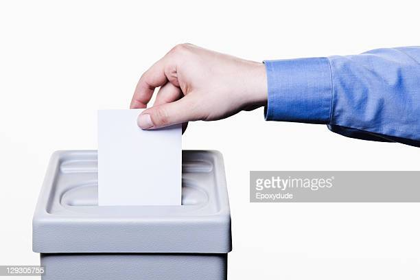 A man putting a blank white ballot into a ballot box, close-up hands