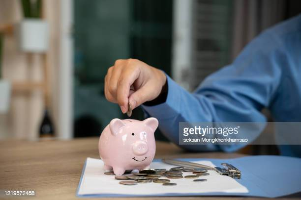 man putting a coin into a pink piggy bank concept for savings and finance - retirement stock pictures, royalty-free photos & images