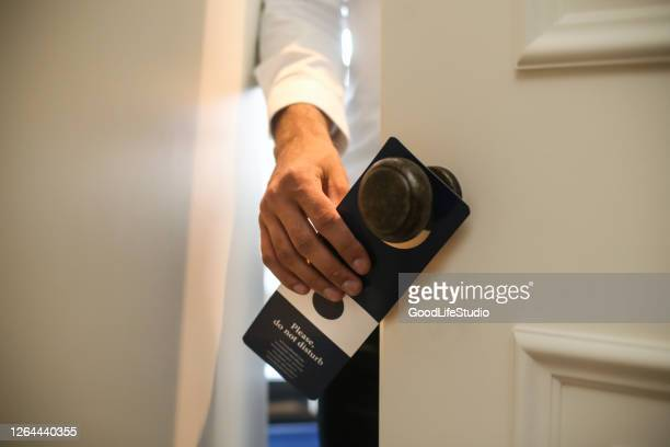 man putting a do not disturb sign - guest stock pictures, royalty-free photos & images