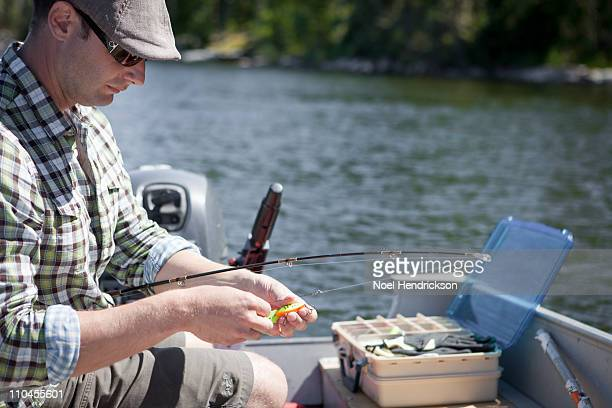 Man putting a fishing hook on his line