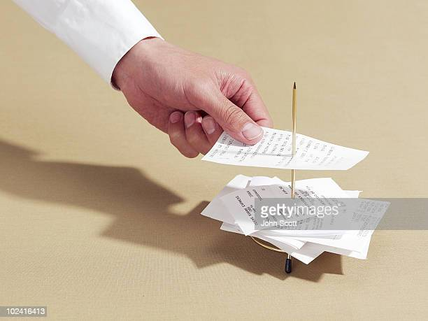 man putting a receipt onto a spike - receipt stock pictures, royalty-free photos & images