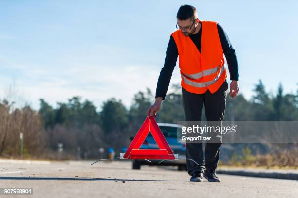 a man putting a warning triangle behind his car - roadside stock pictures, royalty-free photos & images