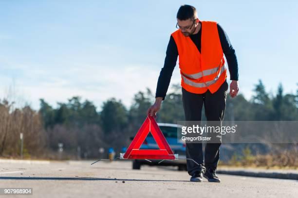 Ein Mann, der ein Warndreieck hinter seinem Auto