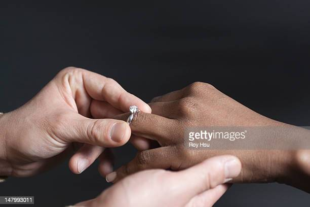 Man putting a wedding ring on a woman's finger