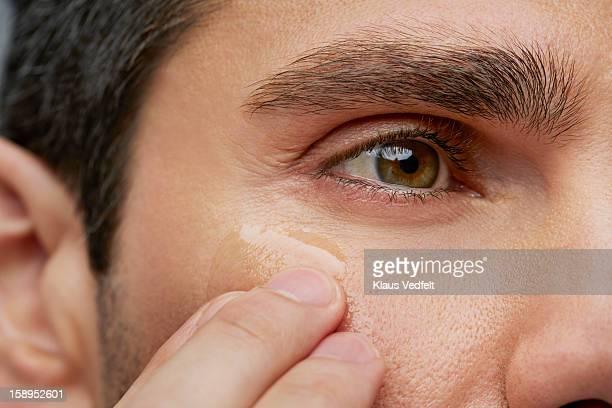 Man putting anti wrinkle gel around the eyes