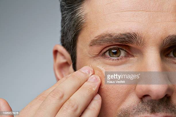 man putting anti wrinkle gel around the eyes - metrosexual stock pictures, royalty-free photos & images