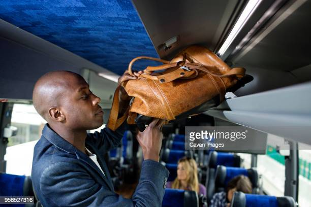 man putting bag in luggage rack in bus - luggage rack stock photos and pictures