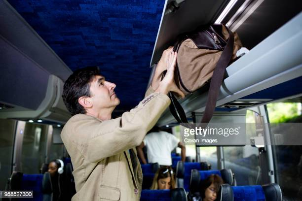 man putting bag in luggage rack while standing in bus - luggage rack stock photos and pictures