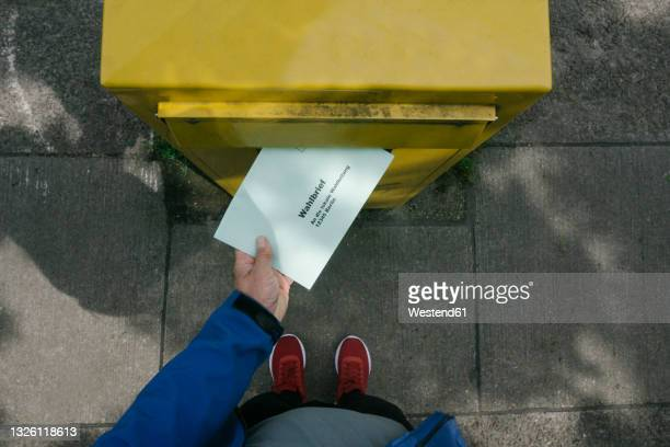 man putting ballot letter in mailbox - germany stock pictures, royalty-free photos & images