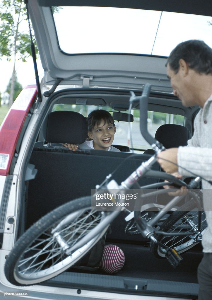 Man putting bicycle into trunk of car, girl in car turning around smiling at man : Stockfoto