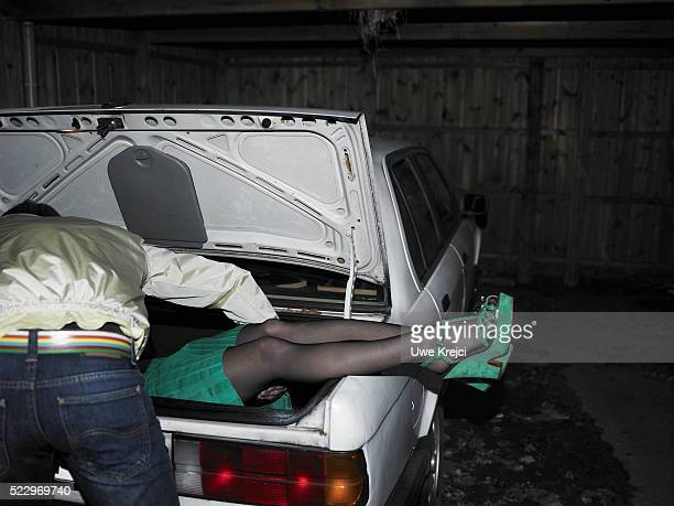 Man Putting Body of Woman in Trunk