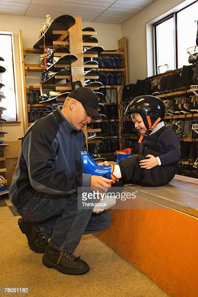 Man putting boots on boy in ski shop