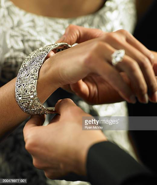 Man putting bracelet around woman's wrist (focus on bracelet)