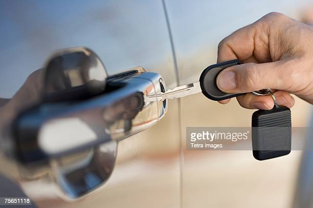 Man putting car key in door