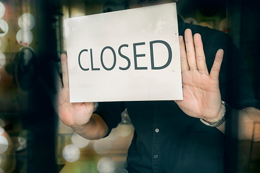 Man putting closed sign in window in shop. Late at night in city. 1139281563
