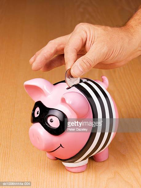 man putting coin into burglar piggy bank on wood grain, close-up of hand - putting stock pictures, royalty-free photos & images