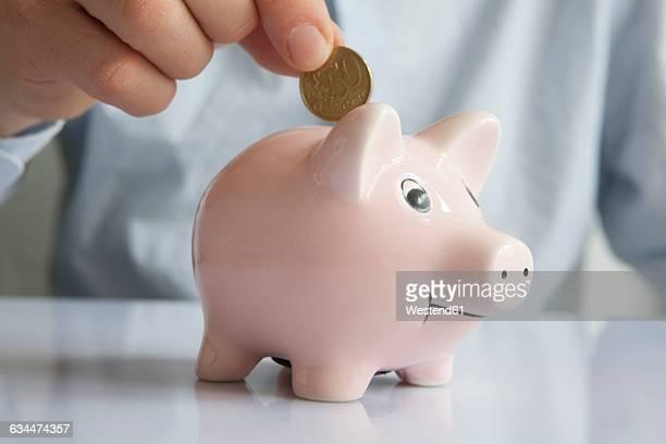 Man putting coin into piggy bank, close-up
