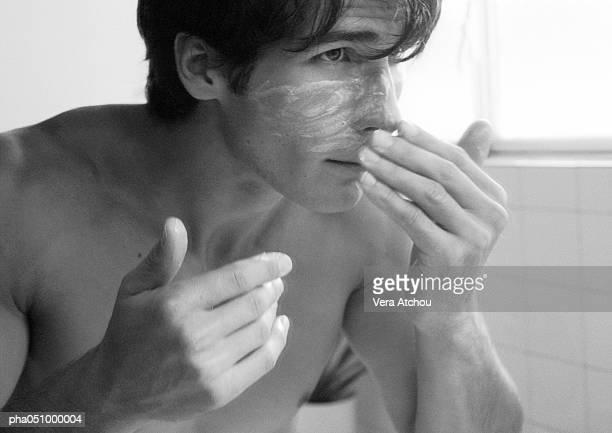 man putting cream on face, b&w - macho fotografías e imágenes de stock