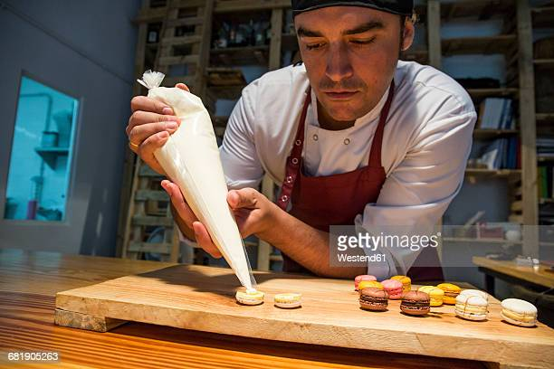 Man putting cream with a pastry bag on a macaron