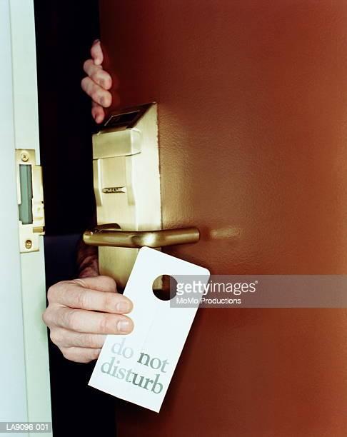 Man putting 'do not disturb' sign on door handle