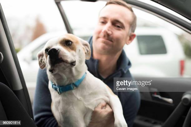 man putting dog in car - alleen één mid volwassen man stockfoto's en -beelden