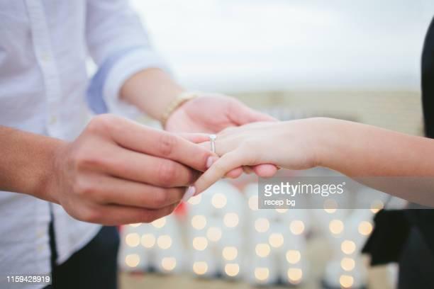 ガールフレンドの指に婚約指輪をはめた男 - 婚約指輪 ストックフォトと画像