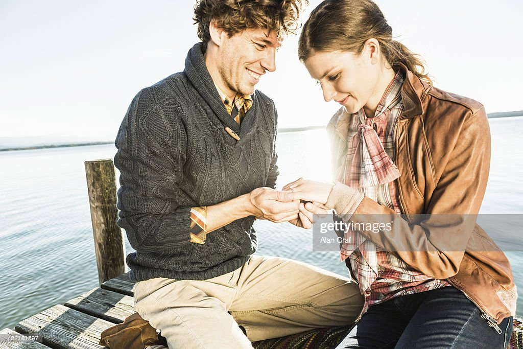 Man putting engagement ring on woman : Stock Photo