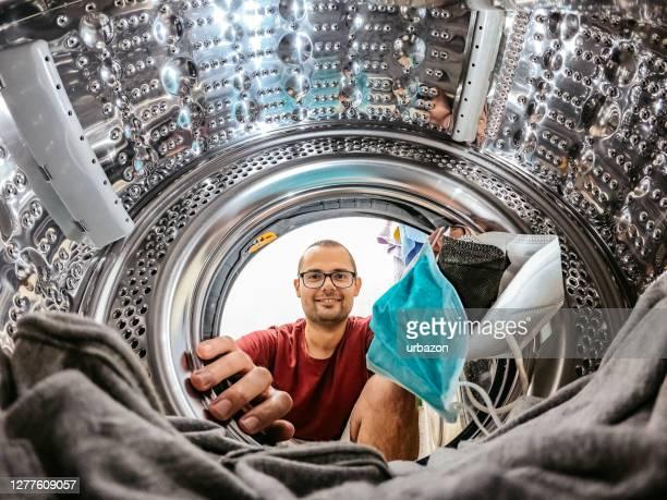 man putting face masks in washing machine - washing machine stock pictures, royalty-free photos & images