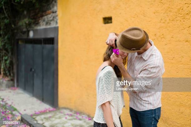 Man putting flower in womans hair, Mexico City, Mexico