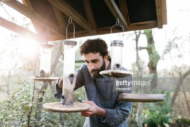Man putting food for the birds in their feeders