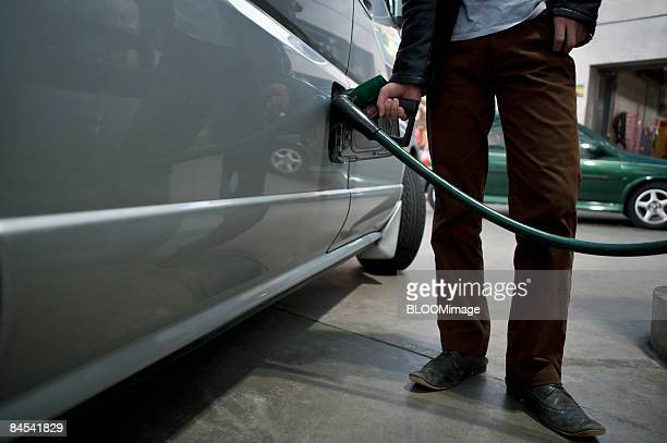 Man putting gas in car, low section