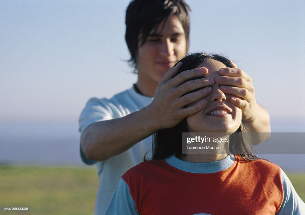 Man putting hands over woman's eyes. : Stockfoto