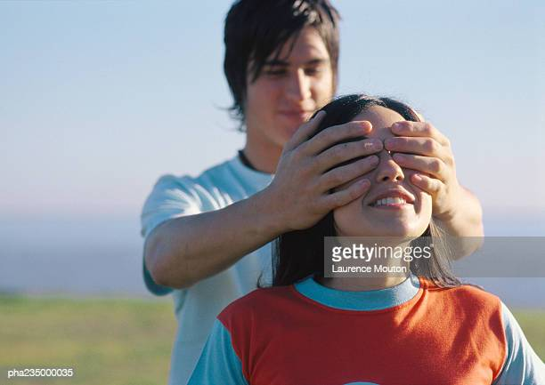 Man putting hands over woman's eyes.