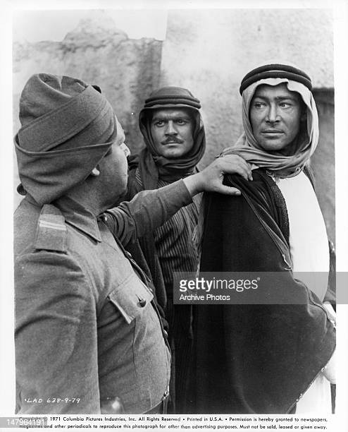 Man putting his hand on the shoulder of Peter O'Toole in a scene from the film 'Lawrence Of Arabia' 1962 Omar Sharif stands behind