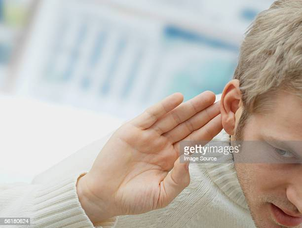 Man putting his hand to his ear