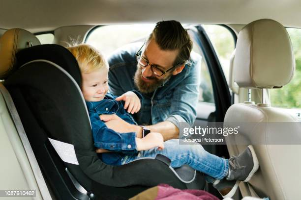 man putting his son into car seat - family inside car stock photos and pictures