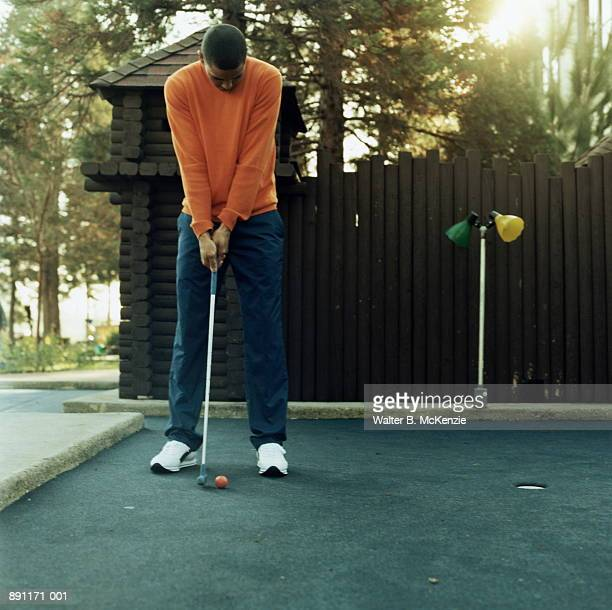 Man putting in front of miniature fort at mini golf course