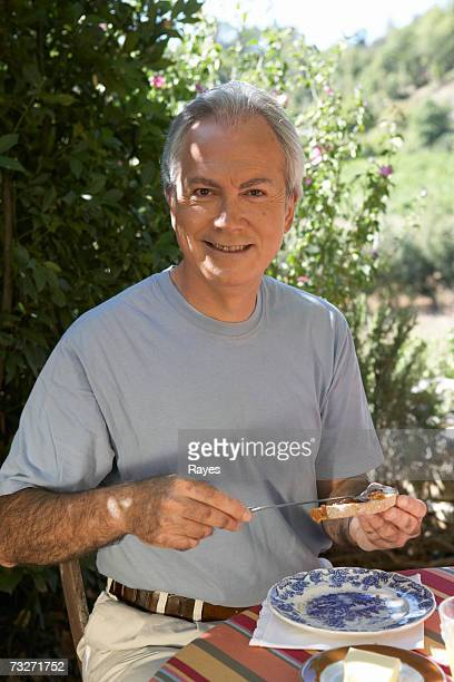 Man putting jam on bread at picnic table