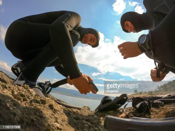 homme mettant des poids de plomb sur la ceinture de plongée - ceinture accessoire photos et images de collection